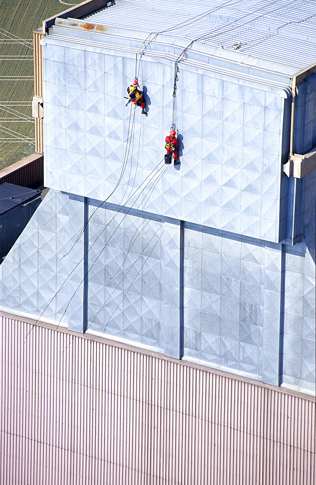 Two workers secured with ropes working on vertical metal surface, renovation works, Duernrohr power plant, Zwentendorf an der Donau, Lower Austria