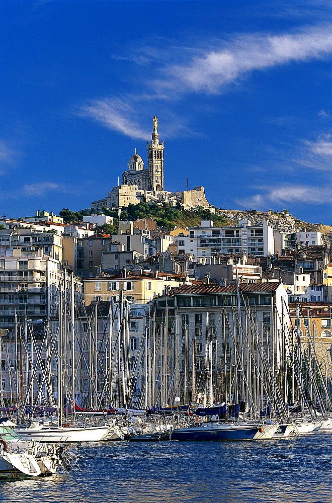 Sailing boats at harbour and the church Notre-Dame-de-la-Garde under clouded sky, Vieux Port, Marseille, Bouches-du-Rhone, Provence, France, Europe