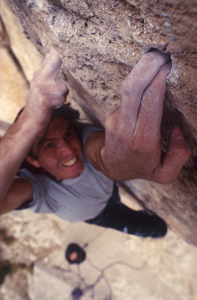 Climber grabbing onto hole, Dolomites, Douth Tyrol, Italy