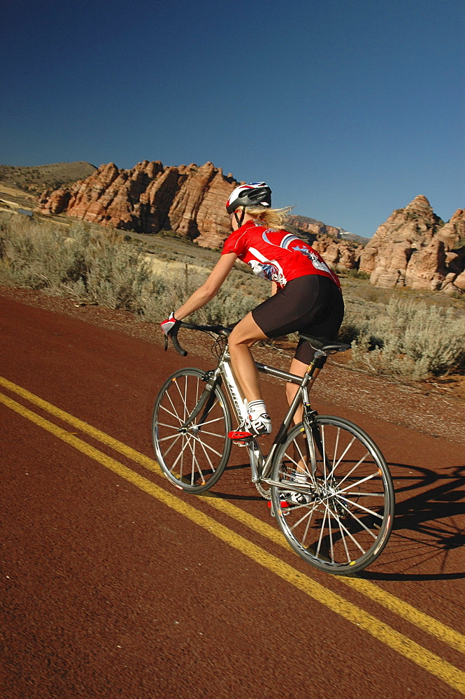 Woman on a racing bike through Zion National Park, Springdale, Utah, USA