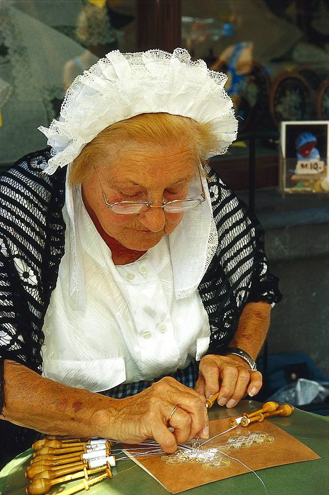 Lacemaker wearing traditional costumes, Bruges, Flanders, Belgium, Europe