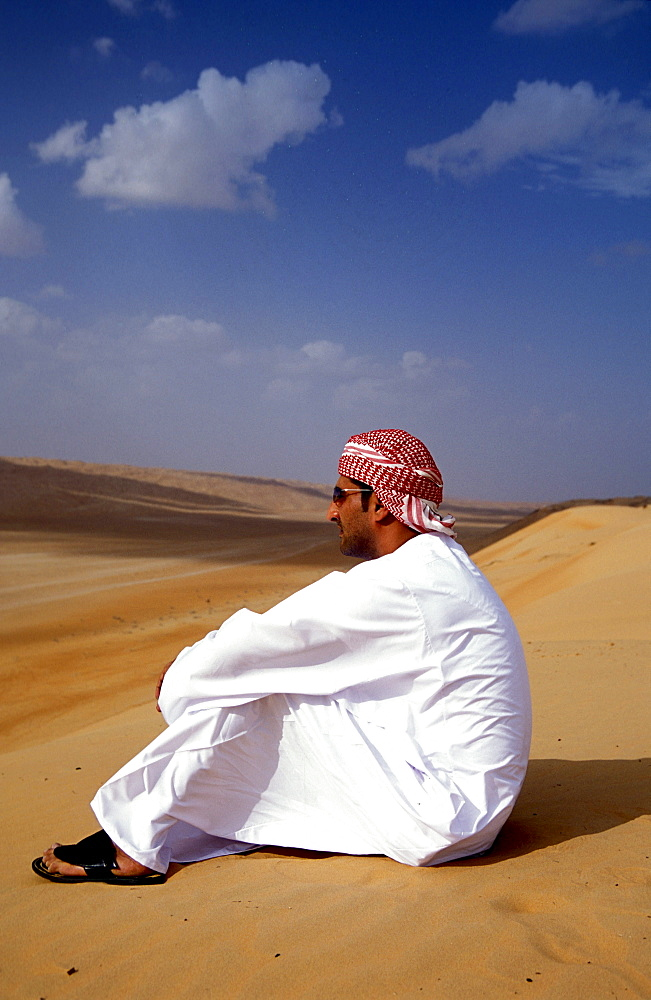 Man sitting in the sand at the desert, Sultanat Oman, Middle East, Asia