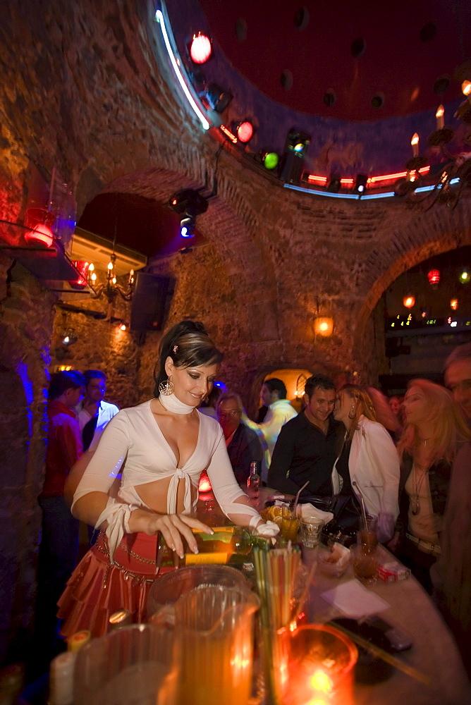 Young woman preparing drinks in the nightclub Hamam Club, Kos-Town, Kos, Greece