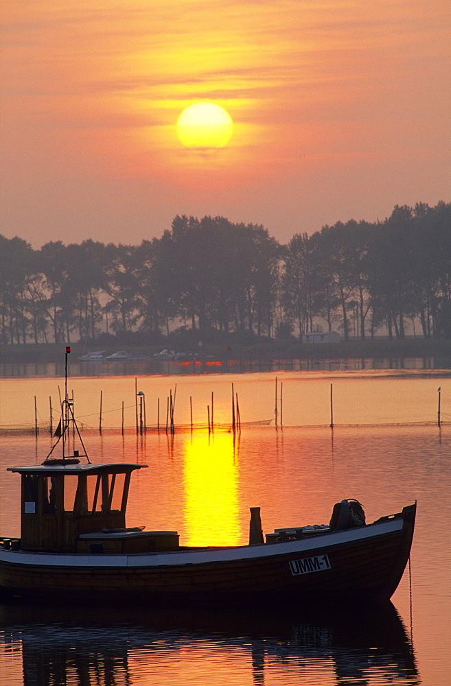 Europe, Germany, Mecklenburg-Western Pomerania, isle of Ruegen, Waase on Ummanz, fishing boat at sunset.