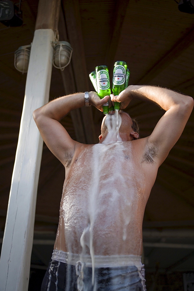 Man drinking four bottles of beer all at once during a beach party of the Super Paradise Club at Super Paradise Beach, knowing as a centrum of gays and nudism, Psarou, Mykonos, Greece