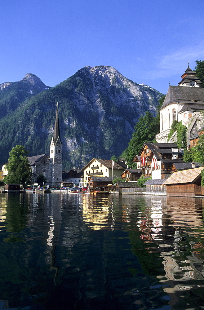 Hallstatt with evangelist and catholic church and reflections in lake Hallstaetter See, Salzkammergut, Upper Austria, Austria