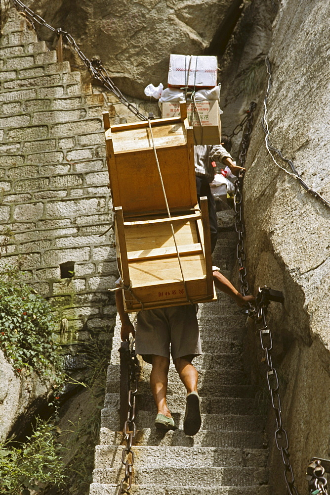 porters carry furniture, building material on their backs up steep mountain steps to the summit, Taoist mountain, Hua Shan, Shaanxi province, Taoist mountain, China, Asia