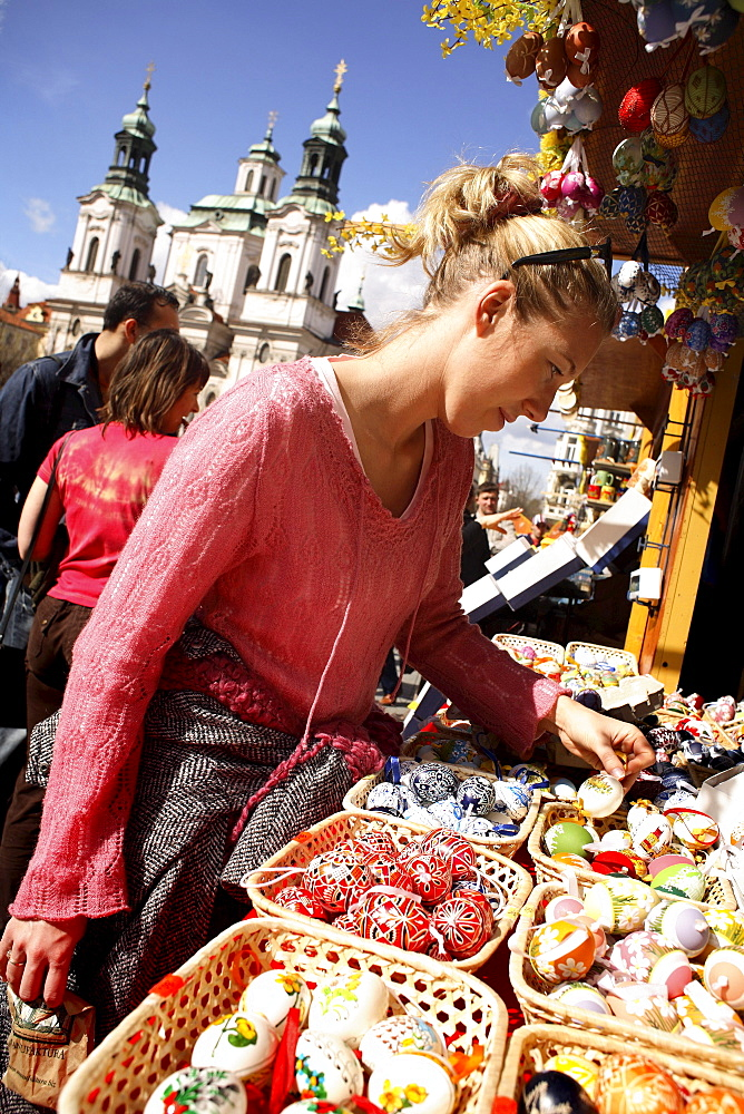 Woman buying Easter eggs at the Easter Market, Old Town Square, Staromestske Namesti, Stare Mesto, Prague, Czech Republic