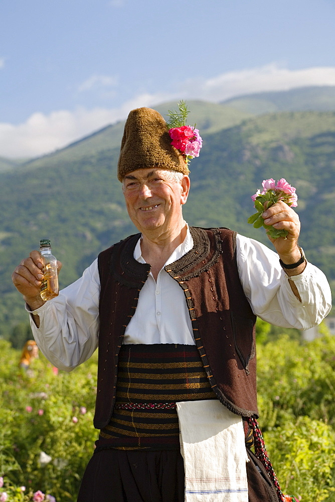 Bulgarian man in traditional costume with rose oil and roses, Rose Festival, Karlovo, Bulgaria, Europe