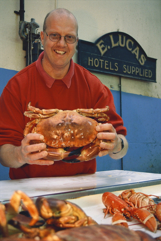 Man selling crabs at a fish market in St. Peter Port, Guernsey, Channel Islands, Great Britain