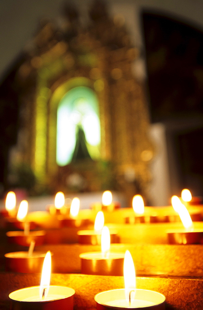sacrifice candles and altar with picture of the Virgin Mary out of focus, Chiesa di San Stefano, Belluno, Italy