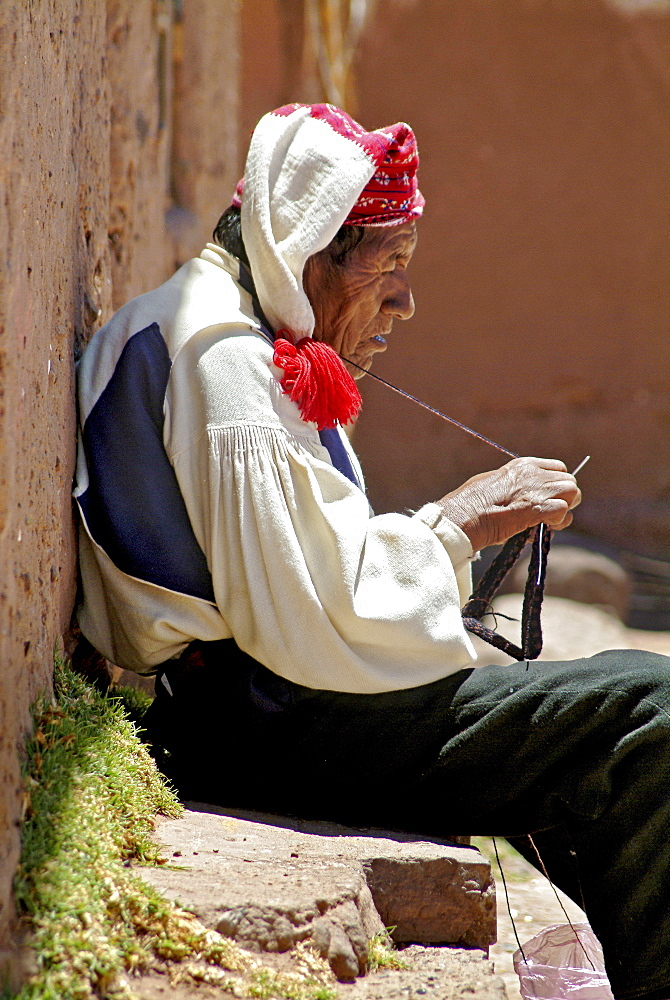 Indigenous man knitting on the island of Taquille, Lake Titicaca, Peru, South America