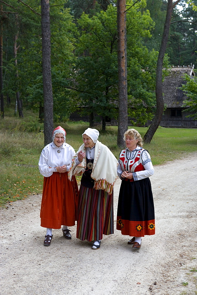 Three ladies in traditional costumes in the farm house museum of Latvia