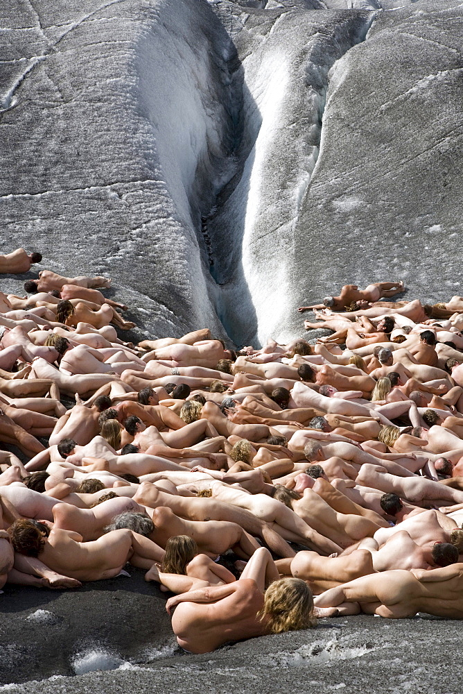 A group of naked people lying on the ice in front of an ice crevasse, around 600 people are posing for Spencer Tunick and Greenpeace on the Aletsch Glacier to protest about climate change, Aletsch Glacier, Valais, Switzerland