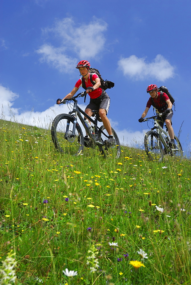 Couple mountain biking on alpine pasture, Bavarian foothills, Bavaria, Germany