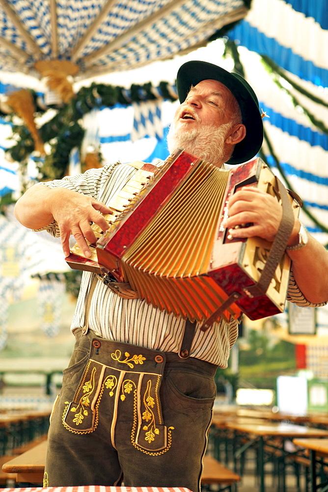 Man wearing bavarian costume playing melodeon