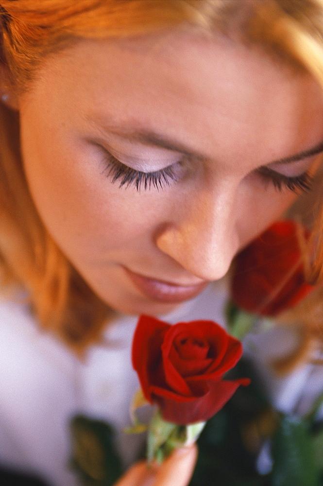 Portrait of a woman smelling a rose, Beauty