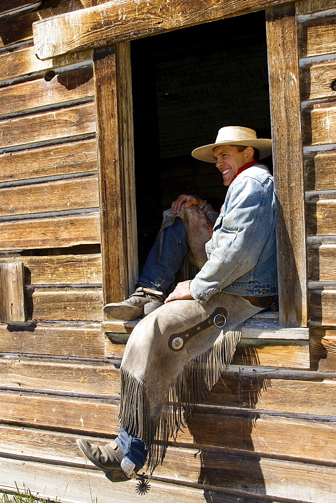 cowboy sitting in barn window, wildwest, Oregon, USA