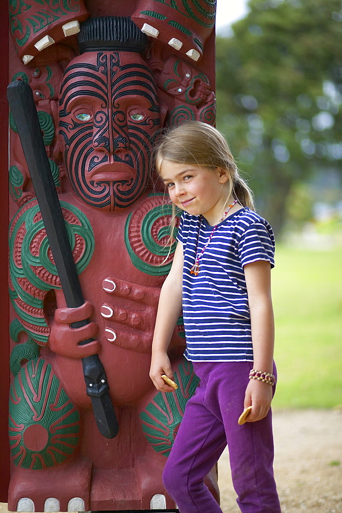 Girl leaning on wooden Maori sculpture, Waitangi Maori Museum, Waitangi, Bay of Islands, Northland, North Island, New Zealand