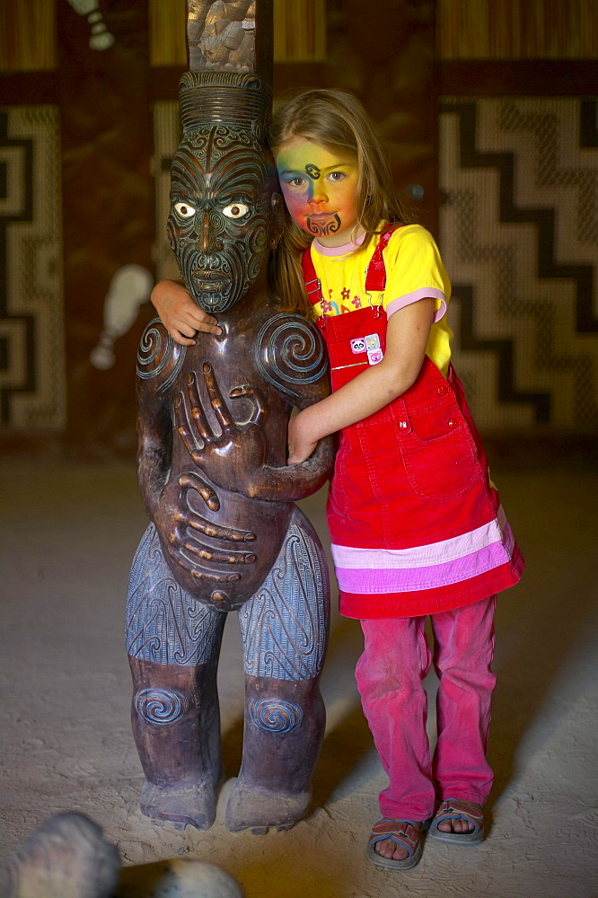 Girl with facepainting (like a Maori Moko - Tatoo), wooden Maori sculpture in Marae, celebrations on Waitangi Day, Okains Bay Museum, Bank`s Peninsula, east coast, South Island, New Zealand