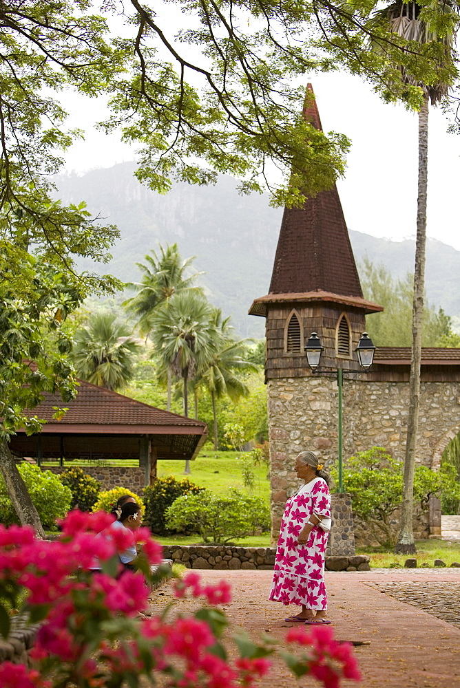 Woman talking in front of the church, Nuku Hiva, Marquesas Islands, Polynesia, Oceania