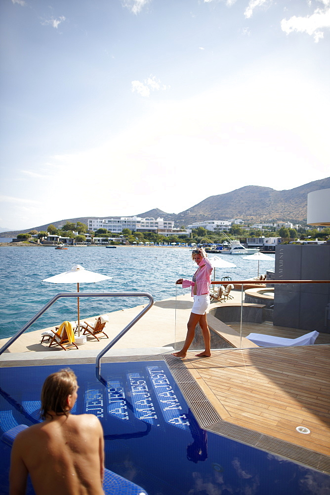 Man and woman at the pool and deck of the Yachting Club Villas, Elounda Beach Resort, Elounda, Crete, Greece