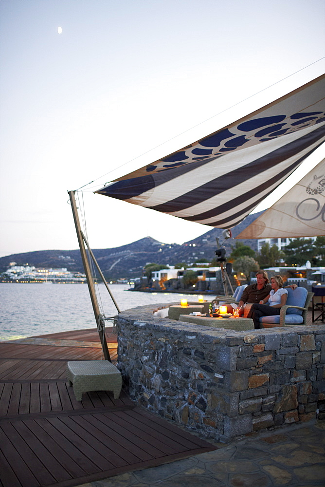 Couple having drinks at the Veghera Bar, Elounda Beach Resort, Elounda, Crete, Greece
