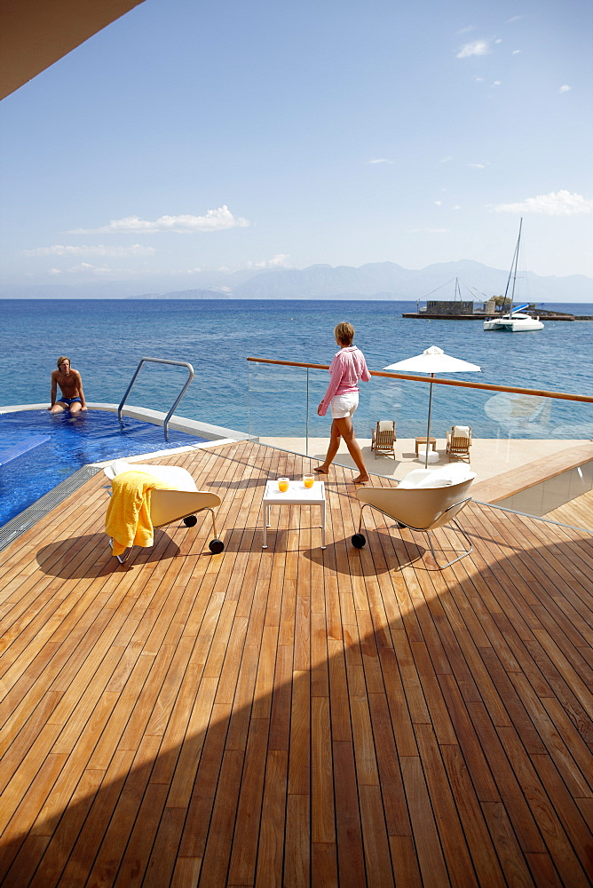 Man and woman at the pool and deck of Yachting Club Villas, Elounda Beach Resort, Elounda, Crete, Greece
