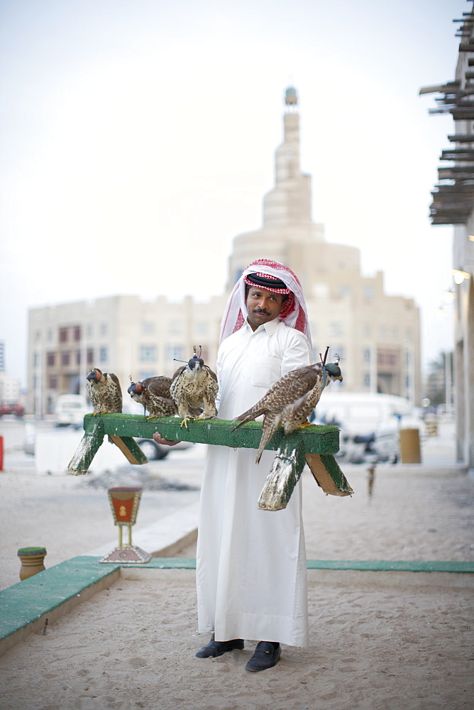 Bird Center salesman with falcons, Islamic Cultural Centre in background, Doha, Qatar