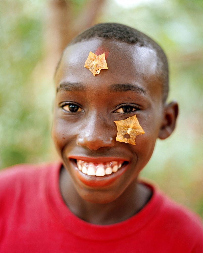 Boy with carambola on his forehead during a Spice Tour on Hakuna Matata Spice Farm, Dole village near Kidichi, north east of Zanzibar Town, Zanzibar, Tanzania, East Africa