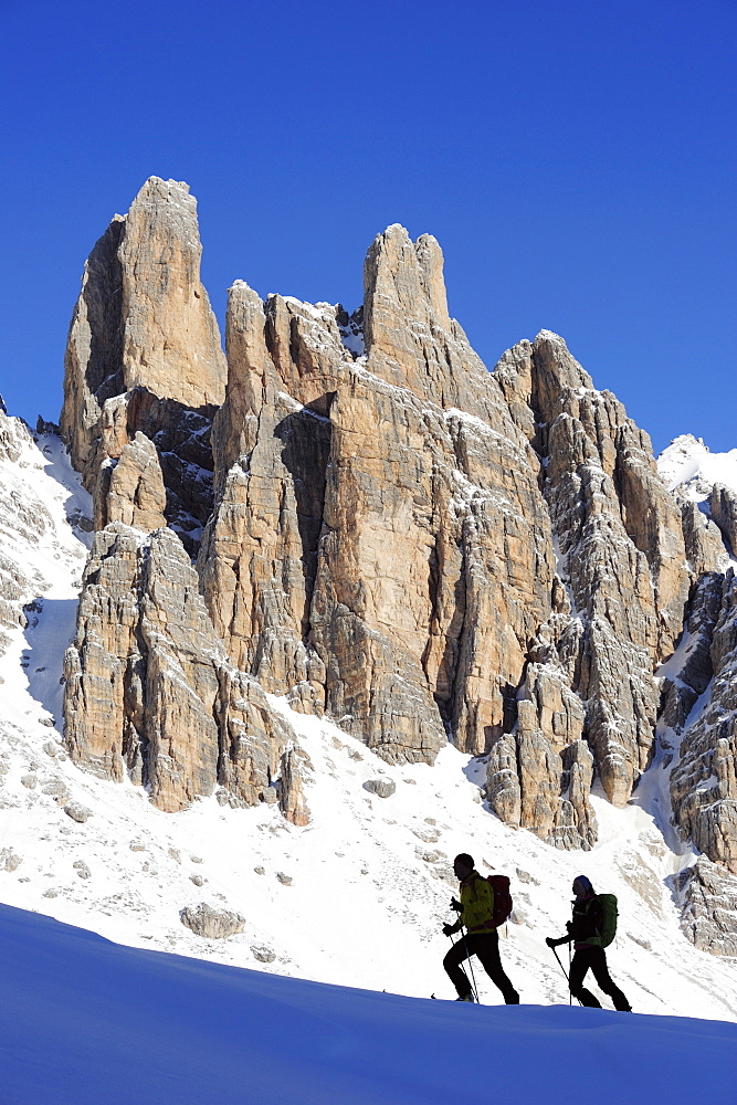 Young woman and young man ascending with crosscountry skis to Corno d'Angolo, rock faces in background, Corno d'Angolo, Cortina, Veneto, Dolomites, Italy, Europe