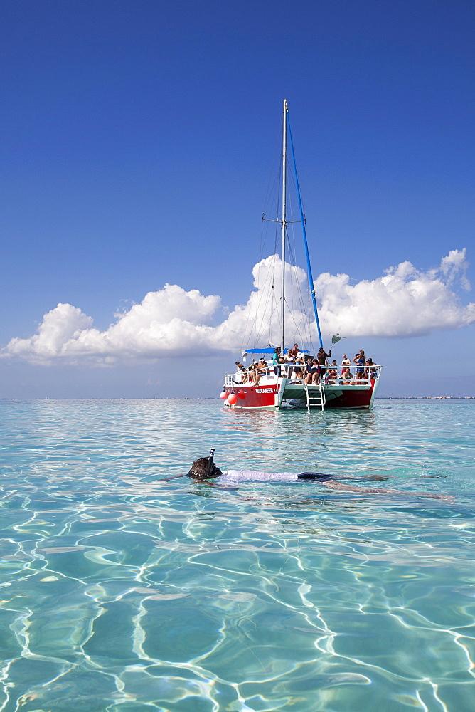 Snorkeler and catamaran sailboat at Stingray City sand bank, Grand Cayman, Cayman Islands, Caribbean