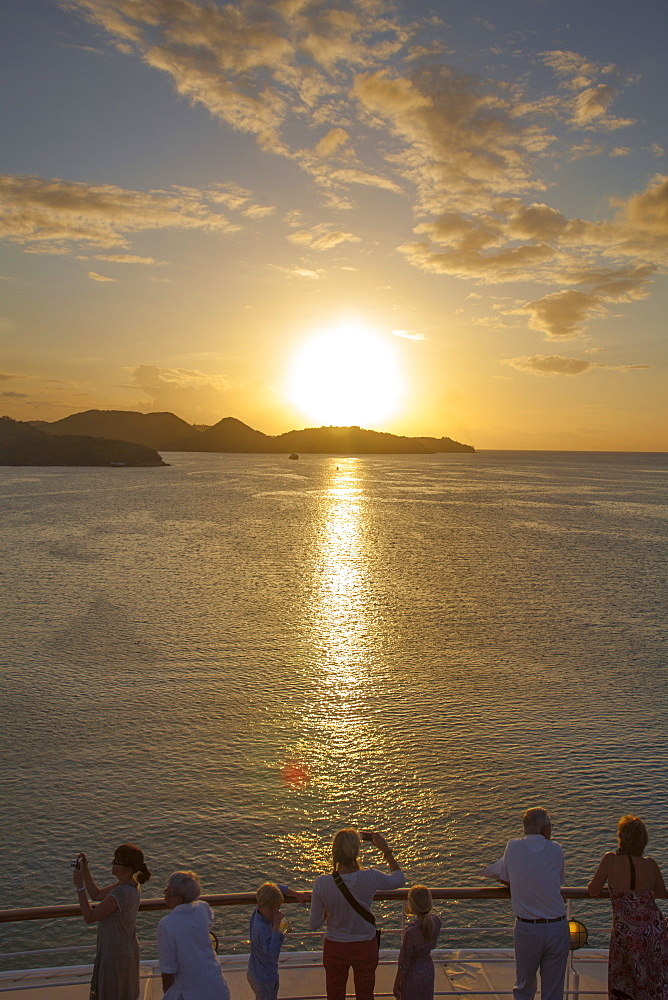 People standing at the railing of cruise ship MS Deutschland (Reederei Peter Deilmann) and admiring the sunset, near St. John's, St. John, Antigua, Antigua and Barbuda, Caribbean