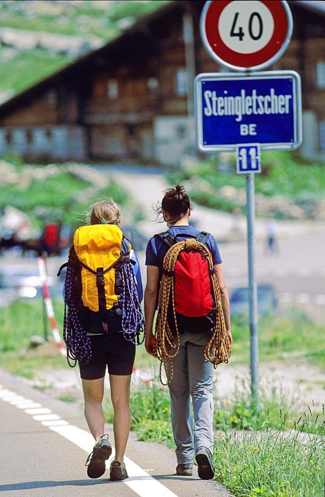 Two young women with climbing equipment walking along street, Bernese Oberland, Canton Bern, Switzerland
