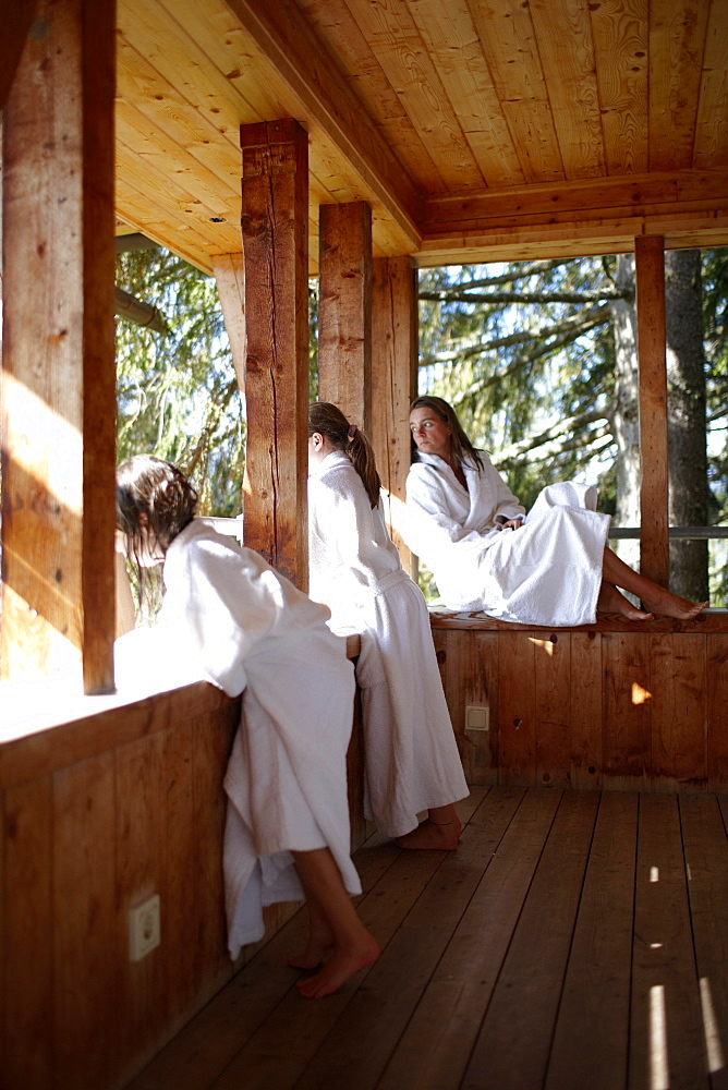 Mother and daughters wearing bathrobes on balcony of a nature hotel, Am Hochpillberg, Schwaz, Tyrol, Austria