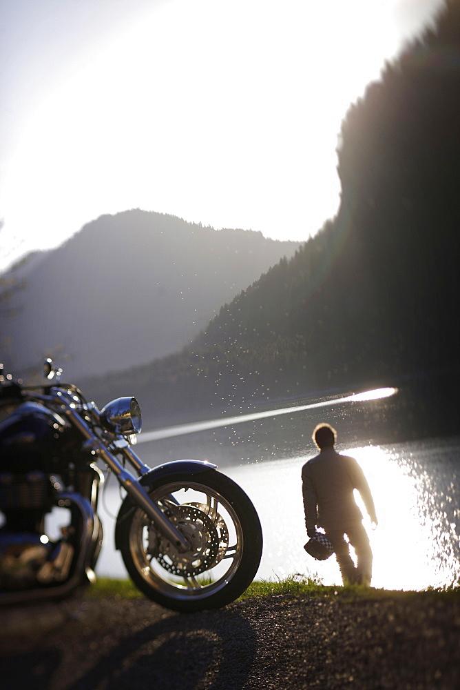 Motorbike tours around Garmisch, Person having a rest at Sylvenstein Reservoir, Upper Bavaria, Bavaria, Germany
