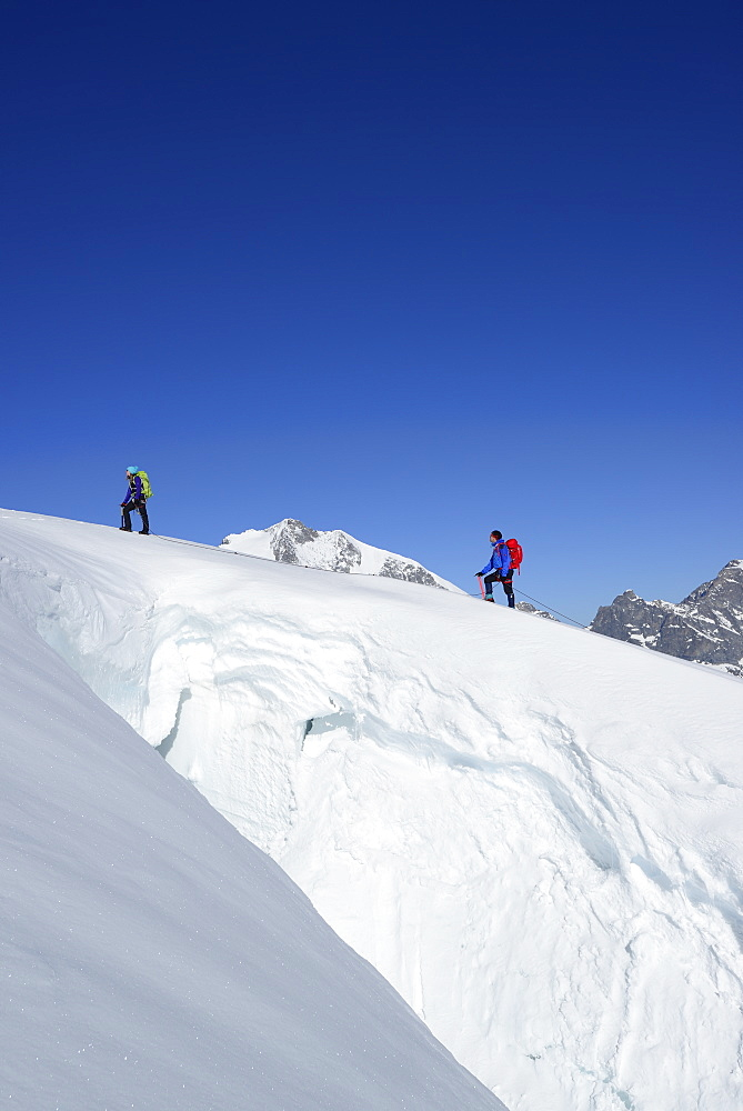 Two mountaineers ascending in front of a crevasse to Piz Palue, Grisons, Switzerland
