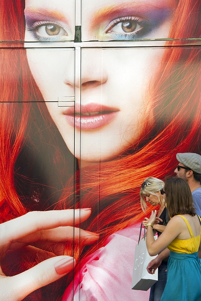 People in front of a giant poster in the shopping area, Strasbourg, Alsace, France