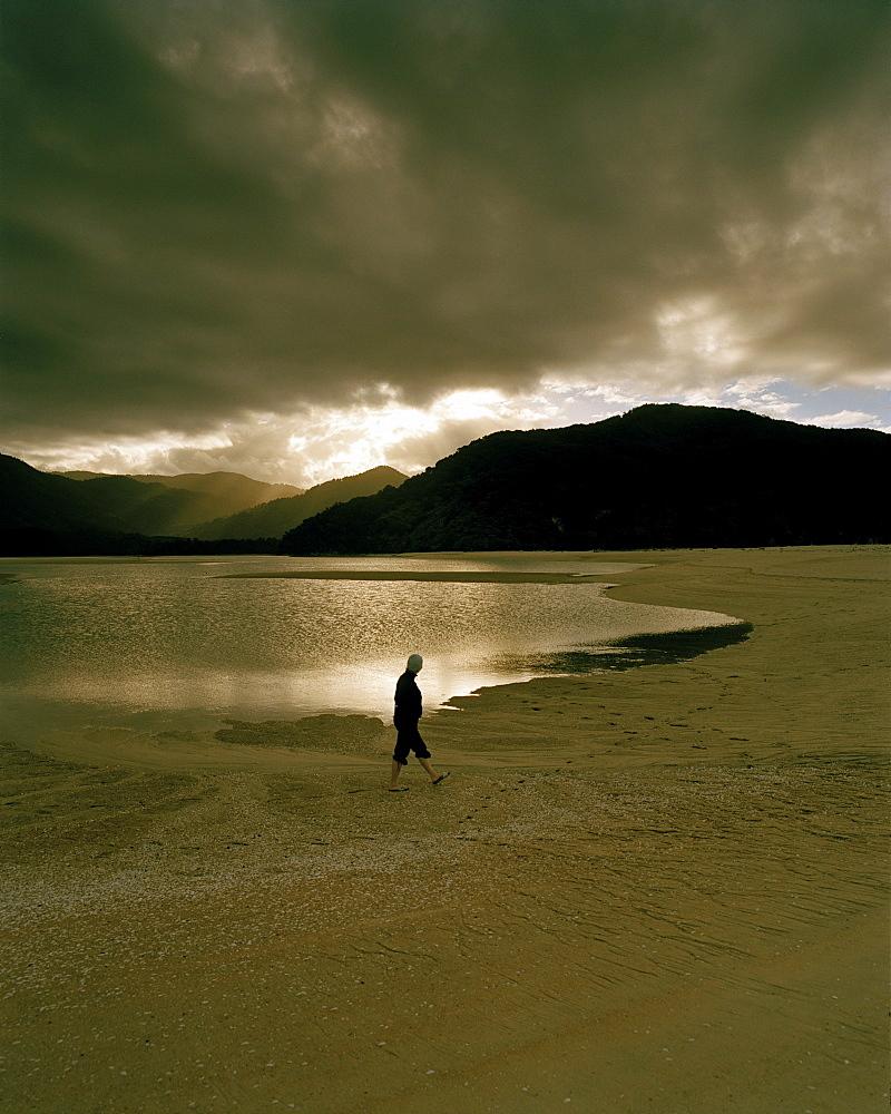A man on shore of Awaroa Inlet at sunset, Abel Tasman National Park, North Coast, South Island, New Zealand