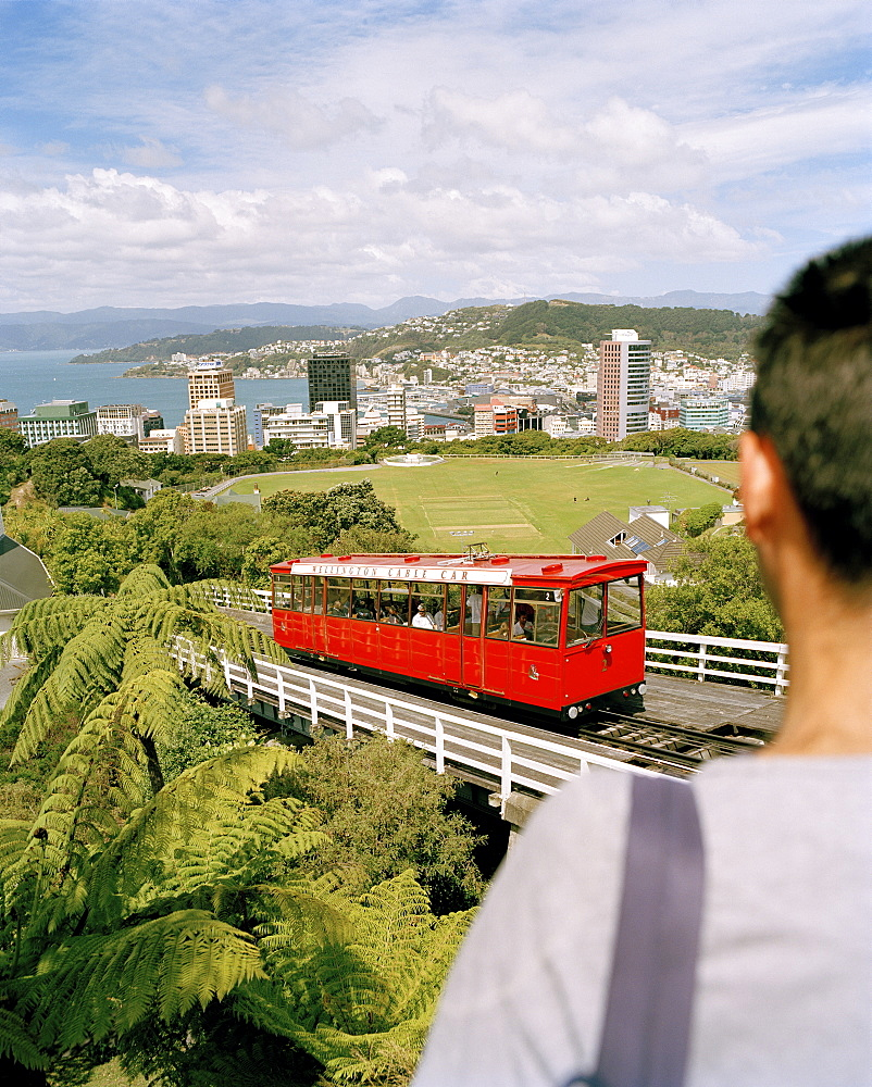 View over cable car at high rise buildings on the waterfront under clouded sky, Wellington, North Island, New Zealand