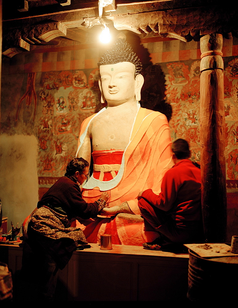 Restorers painting buddha statue in prayers room of convent Tiksey Gonpa, southeast of Leh, Ladakh, Jammu and Kashmir, India