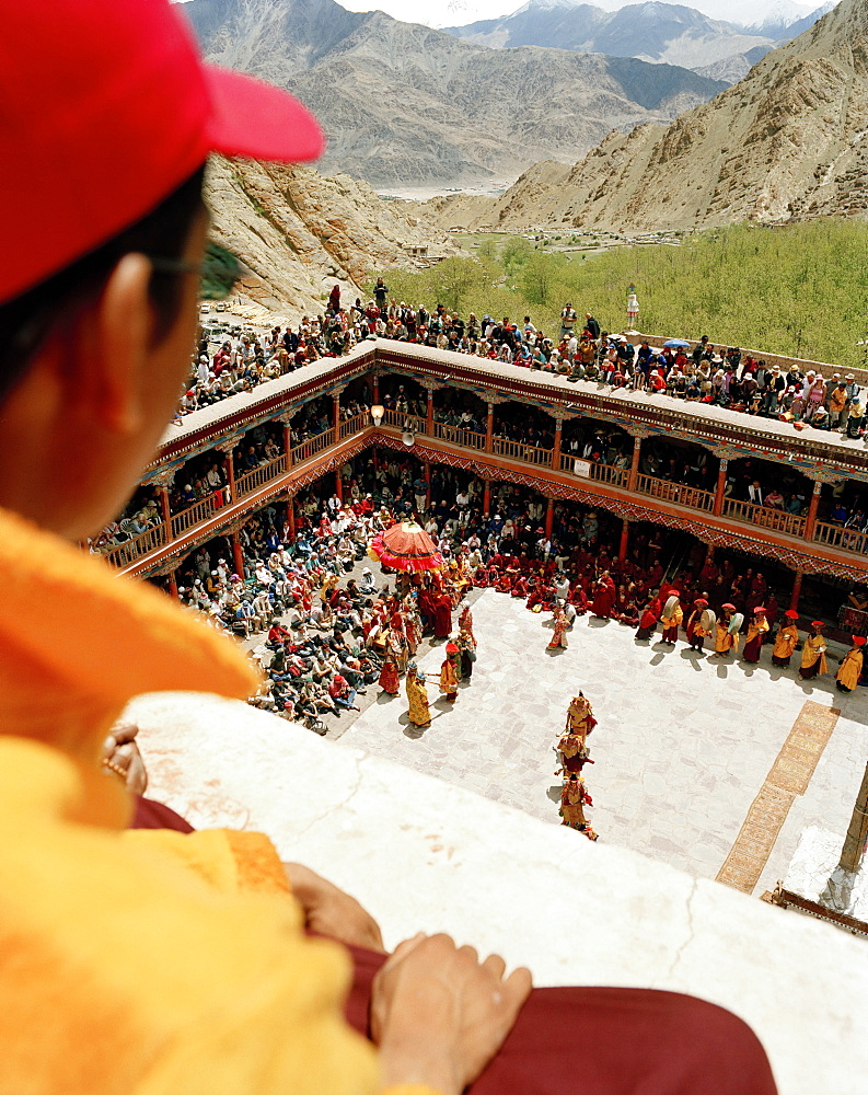 Young monk on the roof looking at the dance of masks in the courtyard during the Hemis Gonpa Festival at convent Hemis, southeast of Leh, Ladakh, Jammu and Kashmir, India