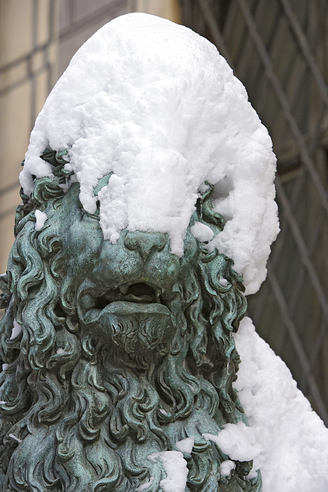 Snow covered lion sculpture in front of entrance of the Residenz palace, Munich, Bavaria, Germany