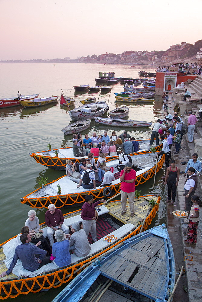 Visitors enter boats at Dasaswamedh Ghat alongside Ganges river, Varanasi, Uttar Pradesh, India