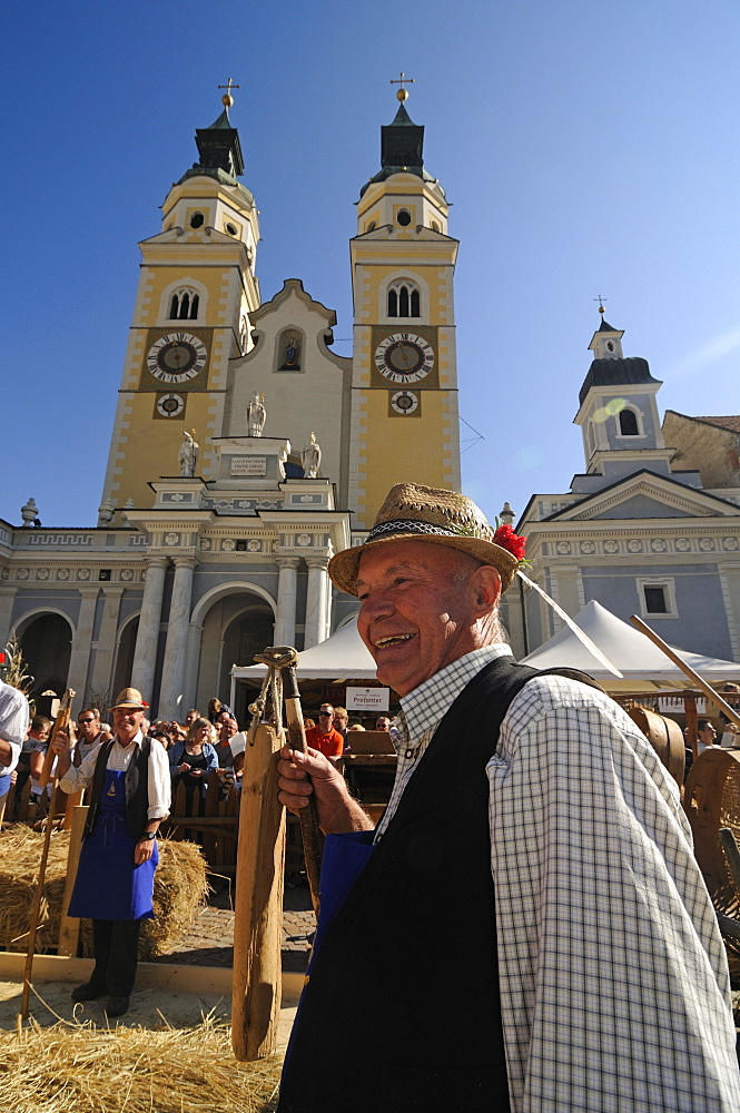 Man threshing corn, Harvest festival on cathedral square, Brixen, South Tyrol, Italy