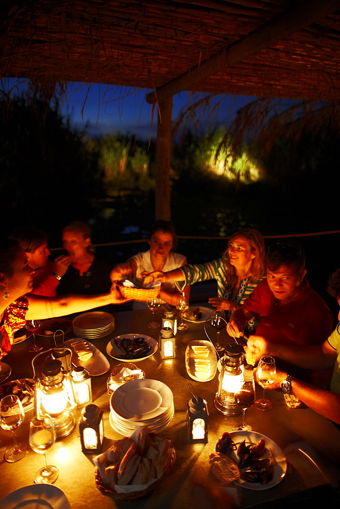 Guests having dinner on the wooden deck at night, Hotel Areias do Seixo, Povoa de Penafirme, A-dos-Cunhados, Costa de Prata, Portugal