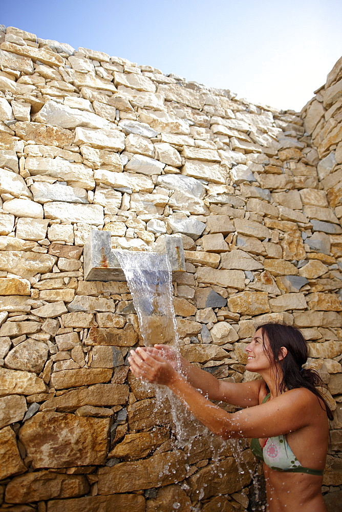 Woman in the outdoor shower with natural stone wall, Hotel Areias do Seixo, Povoa de Penafirme, A-dos-Cunhados, Costa de Prata, Portugal