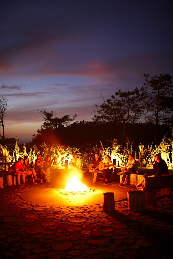 Guests sitting around the camp fire called 'Ring of Fire' in the garden of Hotel Areias do Seixo, Povoa de Penafirme, A-dos-Cunhados, Costa de Prata, Portugal