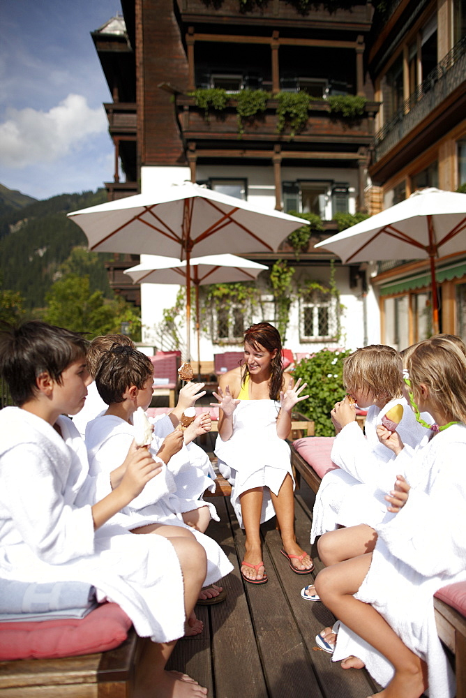 Children sitting on the terrace of Hotel Haus Wirt in bathrobes after swimming, Bad Gastein, St. Johann im Pongau, Salzburg, Austria