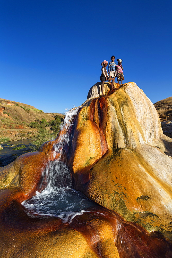 Madagascan children playing in a spouting Geyser, Geysers of Ampefy, highlands, Madagascar, Africa